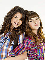 Demi Lovato posing for mags with Selena Gomes