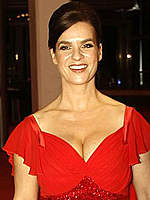Katarina Witt shows cleavage in red dress